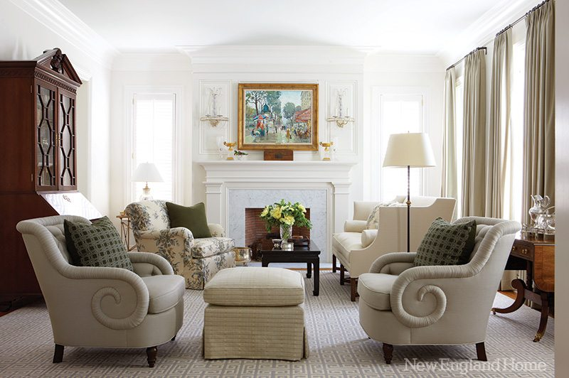 """A hint of blue on the ceiling quietly enhances the living room's airiness, as do the upholstery's neutral tones. """"Nothing is overdone in this house,"""" says designer Amy Aidinis Hirsch. The painting, Parisian Boulevard, is by Constantine Kluge."""