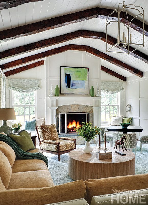 Contemporary abstract art and animal-print upholstery share space with a traditional exposed-beam ceiling and paneled walls in the family room.