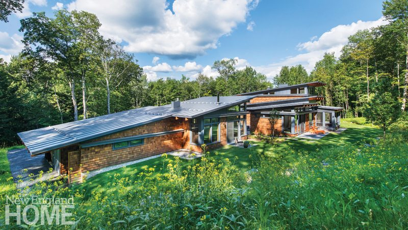Sloping And Overhanging Roofs Help The House Blend Into The Landscape.
