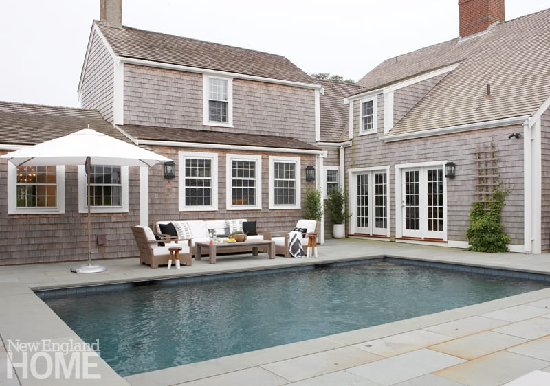 The exterior with a pool surrounded by wood patio furniture adorned with white cushions